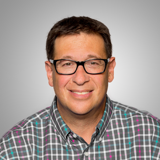 Photo of Scott Pansky wearing a plaid button down shirt and glasses